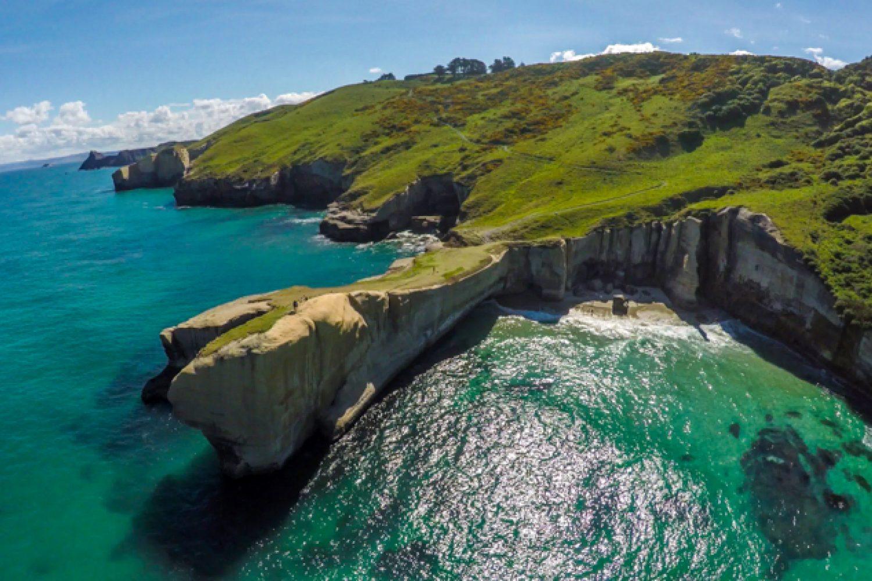 Der Tunnel Beach bei Dunedin. Ganz anders als in Central Otago, ist die Küste bei Dunedin sattgrün, ein Resultat des feucht-nebeligen Klimas.