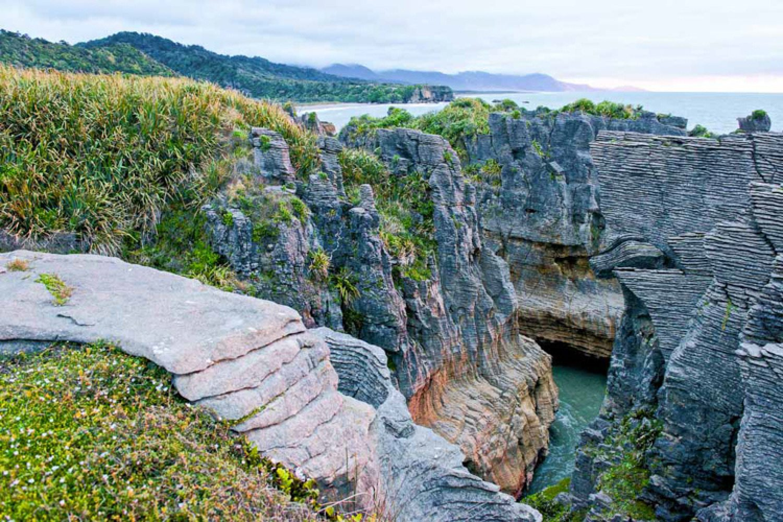 """Die Steinformation an der Westküste trägt den außergewöhnlichen Namen """"Pancake Rocks"""", da ihre Form an aufgeschichtete Pfannkuchen erinnert."""